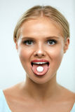 Beautiful Smiling Woman Taking Medicine, Holding Pill On Tongue Royalty Free Stock Image