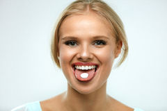 Beautiful Smiling Woman Taking Medicine, Holding Pill On Tongue Royalty Free Stock Photo