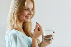 Beautiful Smiling Woman Taking Vitamin Pill. Dietary Supplement Stock Photos