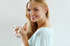 Beautiful Smiling Woman Taking Vitamin Pill. Dietary Supplement royalty free stock images