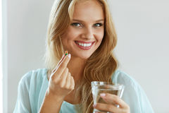 Beautiful Smiling Woman Taking Vitamin Pill. Dietary Supplement. Healthy Diet Nutrition. Portrait Of Beautiful Smiling Young Woman Taking Vitamin Pill. Closeup Stock Photos