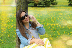 Beautiful smiling woman  talking on mobile phone. Portrait of young, beautiful, smiling woman,  talking on mobile phone, outdoors.  It's a sunny spring day - joy Royalty Free Stock Images