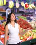 Beautiful smiling woman tosses apple in air. Pretty brunette woman tosses apple in air at farmers market Royalty Free Stock Photography