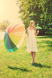 Beautiful smiling woman with two rainbow umbrellas, outdoors Stock Image