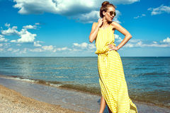 Beautiful smiling woman with updo hair wearing long yellow striped baggy summer dress and round sunglasses walking along the sea Stock Photos