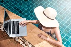 Beautiful smiling woman using laptop computer in swimming pool. Blue water Royalty Free Stock Photos