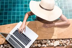 Beautiful smiling woman using laptop computer in swimming pool. Blue water Stock Images