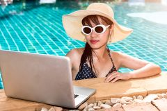 Beautiful smiling woman using laptop computer in swimming pool. Blue water Royalty Free Stock Images