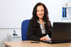 Beautiful smiling woman using laptop in office Stock Photography