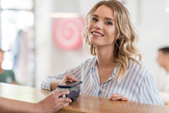 Beautiful smiling woman using smartphone for payment in cafe Stock Photography