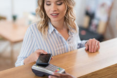Beautiful smiling woman using smartphone for payment in cafe Stock Photos
