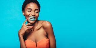 Beautiful smiling woman with vivid makeup. Beautiful african woman with vivid makeup smiling against blue background. Female model wearing artistic makeup royalty free stock images