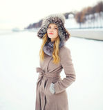 Beautiful smiling woman wearing a coat and hat over snow in winter Stock Images