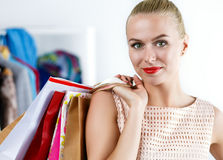 Beautiful smiling woman wearing dress holding colored paper bags Royalty Free Stock Photo