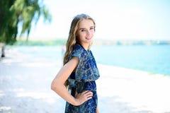 beautiful smiling woman wearing elegant dress standing on beach Royalty Free Stock Images