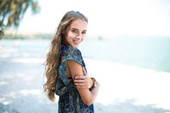 Beautiful smiling woman wearing elegant dress standing on beach Royalty Free Stock Photo