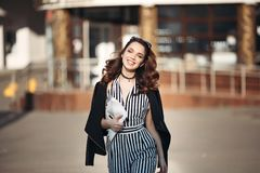 Beautiful smiling woman wearing in striped dress and leather jacket.