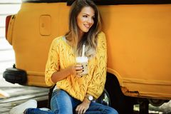 Beautiful smiling woman is wearing yellow sweater drinking coffee latte near old retro bus. Young smiling woman is wearing yellow knitted sweater and jeans is Royalty Free Stock Photos