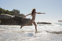 Beautiful smiling woman in white bikini leaping on the beach Stock Image