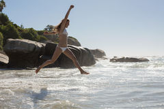 Beautiful smiling woman in white bikini leaping on the beach Royalty Free Stock Images