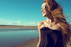 Beautiful smiling woman with the wind in her hair in round mirrored sunglasses standing at the pool looking aside stock photo