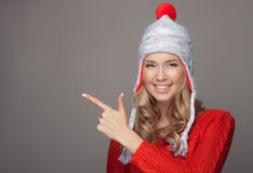 Beautiful smiling woman in winter clothing. Pointing on copyspace. Stock Image