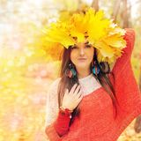 Beautiful smiling woman with wreath of maple leaves on a head Stock Photo