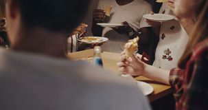 Beautiful smiling young African woman eating pizza and chatting with multiethnic friends at fun house party slow motion. stock video footage