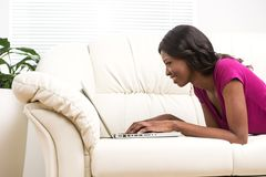 Beautiful smiling young african woman lying on leather sofa at home. Stock Photos