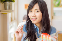 Beautiful smiling young asian woman eating cake Royalty Free Stock Image