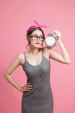 Beautiful smiling young asian woman showing alarm clock on pink Stock Photography