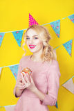 Beautiful smiling young blonde woman with a cake. Celebration and party. Colorful studio portrait with yellow background Stock Photo