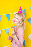 Beautiful smiling young blonde woman with a cake. Celebration and party. Colorful studio portrait with yellow background Royalty Free Stock Images