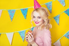 Beautiful smiling young blonde woman with a cake. Celebration and party. Colorful studio portrait with yellow background Royalty Free Stock Photography