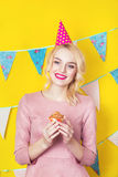 Beautiful smiling young blonde woman with a cake. Celebration and party. Colorful studio portrait with yellow background Stock Photography