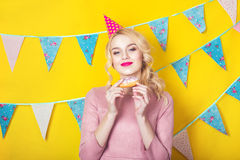 Beautiful smiling young blonde woman with a cake. Celebration and party. Colorful studio portrait with yellow background Royalty Free Stock Photos