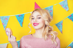 Beautiful smiling young blonde woman with a donut. Celebration and party. Beauty girl taking colorful donuts. Funny joyful woman with sweets, dessert. Diet Royalty Free Stock Images