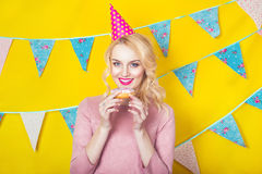 Beautiful smiling young blonde woman with a donut. Celebration and party. Beauty girl taking colorful donuts. Funny joyful woman with sweets, dessert. Diet Royalty Free Stock Photo