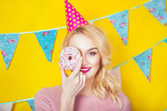 Beautiful smiling young blonde woman with a donut. Celebration and party. Beauty girl taking colorful donuts. Funny joyful woman with sweets, dessert. Diet Royalty Free Stock Image