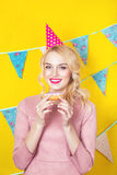 Beautiful smiling young blonde woman with a donut. Celebration and party. Beauty girl taking colorful donuts. Funny joyful woman with sweets, dessert. Diet Stock Image