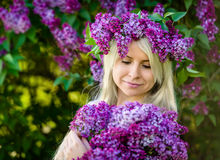 Beautiful smiling young blonde woman is wearing wreath of lilac Royalty Free Stock Image