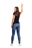 Beautiful smiling young brunette pointing with pencil, back view. Stock Photos