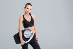 Beautiful smiling young fitness woman in tracksuit holding weigh scale Stock Photography