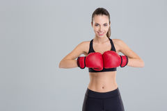 Beautiful smiling young fitness woman wears red boxing gloves Royalty Free Stock Photo