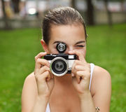 Beautiful smiling young girl with camera Royalty Free Stock Photography