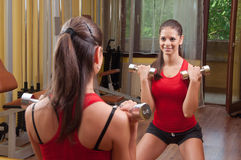 Beautiful smiling young girl exercising in the gym Stock Photography