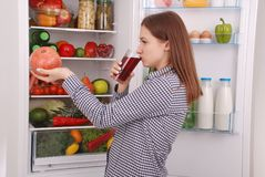 Beautiful smiling young girl holds a glass of pomegranate juice and garnet stock photos