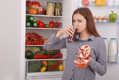 Beautiful smiling young girl holds a glass of pomegranate juice and garnet. On the fridge background stock image