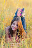 Beautiful smiling young girl lies in the grass. On sunny autumn day Royalty Free Stock Photography