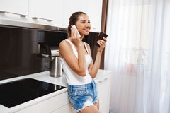 Beautiful smiling young girl  talking on phone at kitchen and drinking a coffee Stock Photography